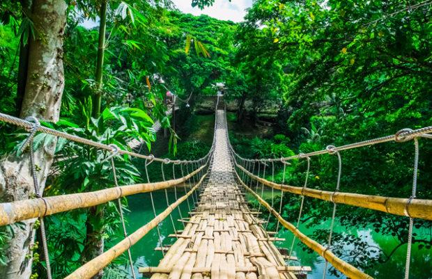 Bamboo pedestrian suspension bridge over river